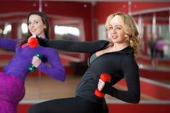 Las muchachas hacen ejercicios del levantamiento de pesas Fotografía de archivo