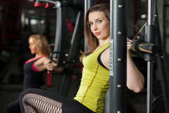 Las muchachas hacen los ejercicios para los brazos y los hombros en gimnasio Foto de archivo
