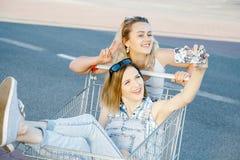 Las muchachas hacen un sephi en una tienda, en un carro de la compra Imagen de archivo libre de regalías