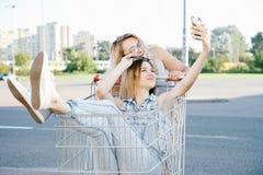 Las muchachas hacen un sephi en una tienda, en un carro de la compra Fotos de archivo libres de regalías