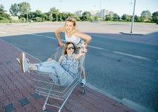 Las muchachas hacen un sephi en una tienda, en un carro de la compra Fotografía de archivo
