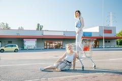 Las muchachas hacen un sephi en una tienda, en un carro de la compra Foto de archivo libre de regalías