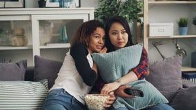 Las muchachas hermosas afroamericano y asiático están mirando la novela de suspense asustadiza en la TV y comiendo las palomitas, almacen de metraje de vídeo