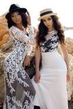 Las muchachas hermosas con el pelo oscuro llevan la ropa elegante casual y el sombrero Imagen de archivo