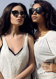 Las muchachas hermosas con el pelo oscuro llevan la ropa elegante casual y las gafas de sol Foto de archivo libre de regalías