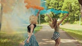 Las muchachas hermosas del inconformista en ropa hermosa corren en el parque que agita humo coloreado almacen de video