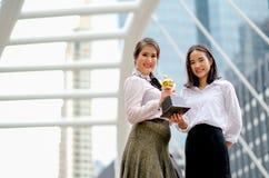 Las muchachas hermosas del negocio muestran su trofeo del éxito en sus trabajos y se colocan entre el alto edificio en la ciudad imagenes de archivo