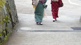 Las muchachas japonesas llevan calzado del parasol del kimono y de la sandalia del geta Japón metrajes