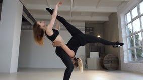 Las muchachas jovenes atractivas del deporte están haciendo la yoga junta Mujeres hermosas que se resuelven en clase de la yoga j almacen de video