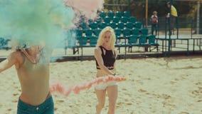 Las muchachas jovenes del inconformista en pantalones cortos corren en el campo de la arena que agita humo coloreado almacen de metraje de vídeo