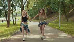 Las muchachas lindas del inconformista en pantalones cortos saltan en parque Las chicas jóvenes se divierten y al aire libre almacen de metraje de vídeo