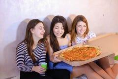 Las muchachas lindas frescas pasan tiempo y gozan de la pizza, se sientan en piso en bergantín Fotos de archivo libres de regalías
