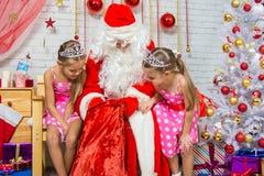 Las muchachas miran en el bolso de Santa Claus Fotografía de archivo