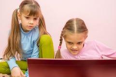 Las muchachas miran la pantalla un poco cansada de la visión Foto de archivo libre de regalías