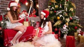 Las muchachas preparan tarjetas del ` s del Año Nuevo y los regalos a los amigos, dos amigos embalan las cajas festivas cerca del metrajes