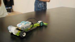 Las muchachas pusieron sus coches plásticos en la tabla para buscar cómo moverlos usando la cámara lenta de los ipads almacen de video