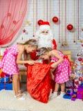 Las muchachas que cavan en el bolso con los regalos que trajeron a Santa Claus Fotografía de archivo libre de regalías