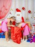 Las muchachas que cavan en el bolso con los regalos Santa Claus Foto de archivo libre de regalías