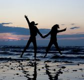Las muchachas que saltan cerca del mar. Fotografía de archivo