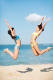 Las muchachas que saltan en la playa Foto de archivo libre de regalías