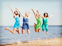 Las muchachas que saltan en la playa Foto de archivo