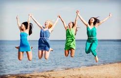 Las muchachas que saltan en la playa Imagen de archivo libre de regalías