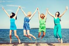 Las muchachas que saltan en la playa Imagenes de archivo
