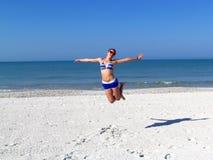 Las muchachas que saltan en la playa arenosa Fotografía de archivo libre de regalías