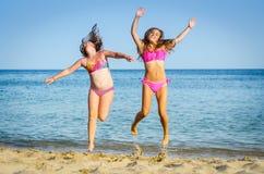 Las muchachas que saltan en la playa tropical Foto de archivo