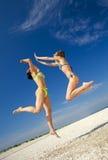 Las muchachas que saltan en una playa Foto de archivo libre de regalías