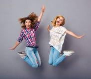 Las muchachas que saltan sobre fondo gris Fotos de archivo
