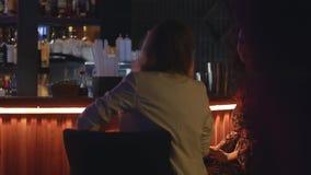 Las muchachas que se sientan en el standon de la barra van de fiesta en club nocturno luces alineada holidays bebida metrajes