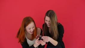 Las muchachas que toman el autorretrato con las fotos elegantes del reloj del teléfono sonríen y ríen Cámara lenta Fondo rojo del metrajes