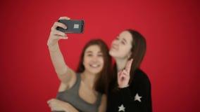 Las muchachas que toman el autorretrato con las fotos elegantes del reloj del teléfono sonríen y ríen Fondo rojo del estudio almacen de video