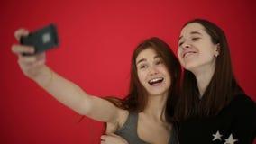 Las muchachas que toman el autorretrato con las fotos elegantes del reloj del teléfono sonríen y ríen Fondo rojo del estudio metrajes