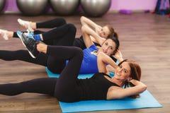 Las muchachas realizan los ejercicios para los músculos abdominales Fotografía de archivo libre de regalías