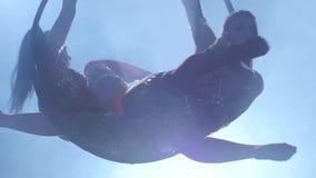 Las muchachas realizan un truco en el aro aéreo Fondo negro del humo Silueta Cámara lenta Cierre para arriba almacen de metraje de vídeo