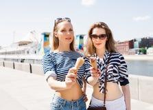 Las muchachas rubias atractivas jovenes de los mejores amigos que comen el helado en tiempo caliente del verano en gafas de sol t Imagenes de archivo