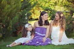 Las muchachas rubias morenas imponentes de las hermanas de los ojos azules de la castaña que llevan el vestido púrpura blanco ele Imágenes de archivo libres de regalías
