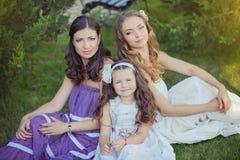 Las muchachas rubias morenas imponentes de las hermanas de los ojos azules de la castaña que llevan el vestido púrpura blanco ele Fotografía de archivo