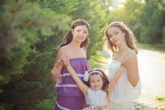 Las muchachas rubias morenas imponentes de las hermanas de los ojos azules de la castaña que llevan el vestido púrpura blanco ele Imagen de archivo libre de regalías
