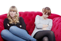 Las muchachas rubias y pelirrojas hermosas jovenes en el sofá rojo tienen un co Imagenes de archivo