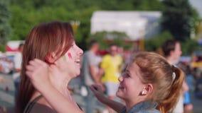 Las muchachas se abrazan feliz durante partido de fútbol de observación en zona de la fan almacen de video