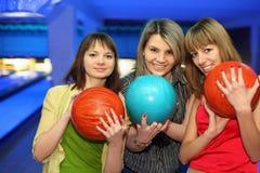 Las muchachas se colocan al costado, sostienen las bolas para el bowling Imágenes de archivo libres de regalías
