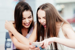 Las muchachas se divierten con un teléfono en café Imagen de archivo