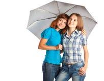 Las muchachas se están colocando bajo el paraguas Imagenes de archivo