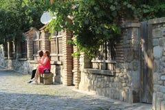 Las muchachas se están sentando en la silla de piedra imagen de archivo
