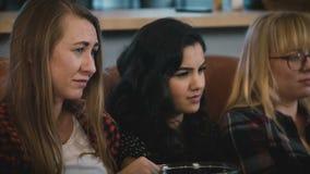 Las muchachas se sientan en el sofá y miran película triste en la TV Señoras europeas hermosas jovenes que miran la película romá metrajes