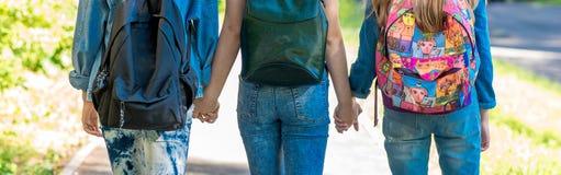 Las muchachas son colegialas En verano en un parque en la ciudad Tres estudiantes Se detienen las manos del ` s Visión posterior  Imagen de archivo