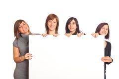 Las muchachas sonrientes sostienen la cartelera en blanco Imágenes de archivo libres de regalías